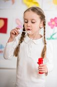 picture of pullovers  - Little pretty girl in white pullover blowing soap bubbles on colorful background - JPG