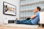 picture of carpet  - Couple Sitting On Carpet Watching Television In Living Room - JPG