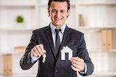 stock photo of model home  - Realtor man is showing a model of home and keys - JPG