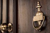 picture of door  - A copper door knocker on a dark brown door. ** Note: Shallow depth of field - JPG