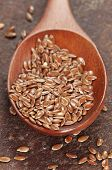 foto of flax seed oil  - Flax seeds in a timber spoon closeup shot - JPG