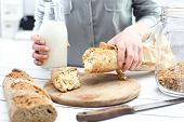 stock photo of hand cut  - Woman hands cutting bread on the kitchen counter  - JPG