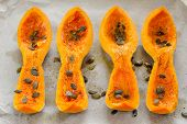 picture of butternut  - Four butternut squash pieces with pumpkin seeds on white paper horizontal topview - JPG