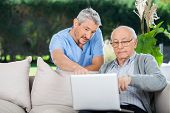 picture of nursing  - Male nurse explaining something on laptop to senior man at nursing home porch - JPG