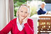 image of beautiful senior woman  - Portrait of beautiful senior woman sitting at nursing home with grandson in background - JPG
