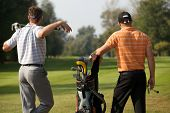 stock photo of golf bag  - Young men standing in golf course by golf bag full of sticks - JPG