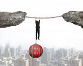 stock photo of shackles  - Businessman shackled by debt concrete ball hanging on iron chains connected two cliffs with urban scene background - JPG