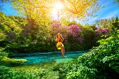pic of sulky  - Happy young woman swinging with bungee above the river in the forest - JPG