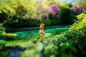 foto of sulky  - Happy young woman swinging with bungee above the river in the forest - JPG