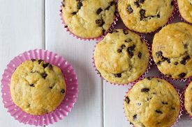 stock photo of chocolate muffin  - Banana Chocolate Chip Muffins from Above with Pink Polka Dot Muffin Paper on a White Wooden Table - JPG