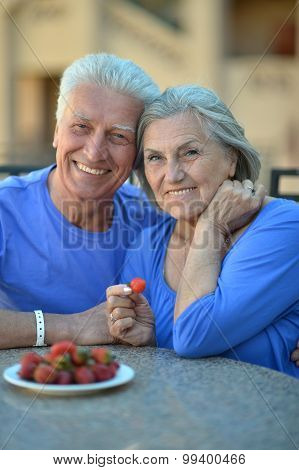 Senior couple in cafe with strawberries