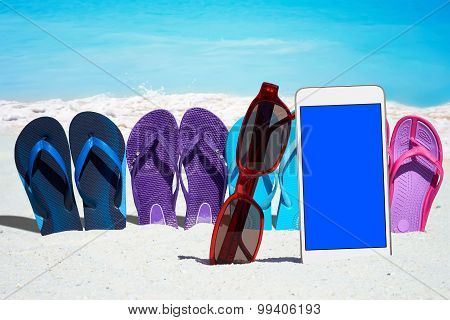 Smartphone And Flip Flops On The Beach