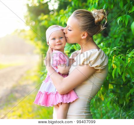 Portrait Of Mother Hug And Kissing Baby Daughter Outdoors In Sunny Summer Day