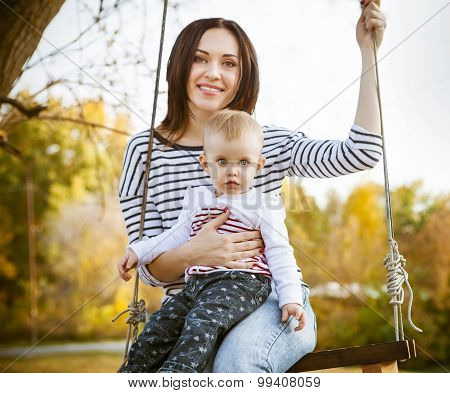 Happy Mother And Her Little Baby Swing In The Autumn Park
