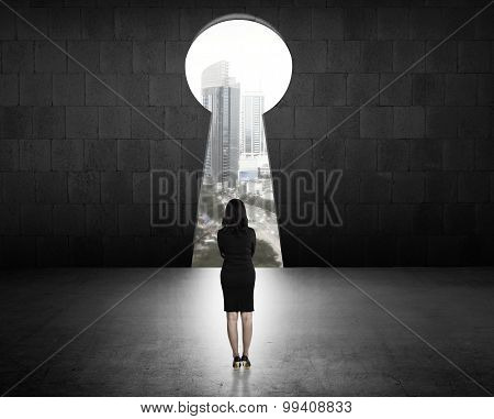 Business Woman Looking Through Key Hole