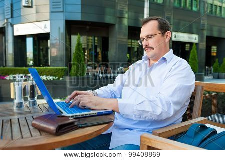 Middle age businessman works on laptop in outdoor cafe