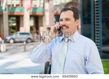 Middle age smiling businessman talking portrait outdoors