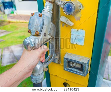 Hand Holding Gasoline Tap.