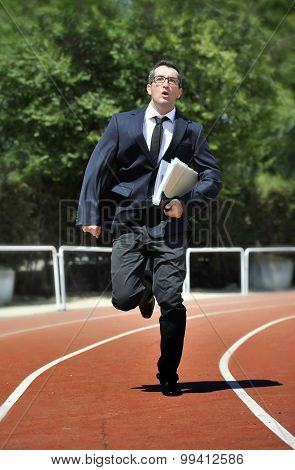 Businessman In Suit And Necktie Carrying Folder Running Desperate In Stress On Athletic Track