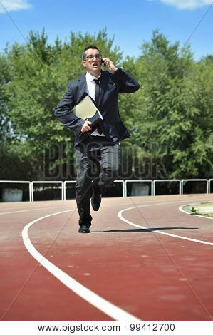 Businessman In Suit And Necktie Carrying Folder In Stress On Athletic Track Talking On Mobile Phone