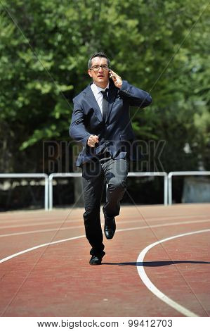 Businessman In Suit And Necktie Running In Stress On Athletic Track Talking On Mobile Phone Overwork