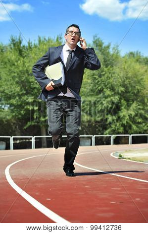 businessman in suit and necktie carrying folder running in stress on athletic track