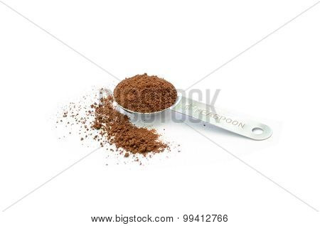 Coffee ground in stainless tea spoon isolated in white background