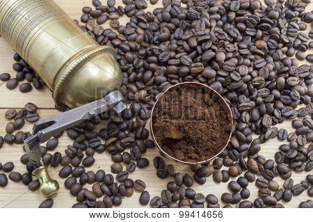 Coffee Beans, Grinder And On A Wooden Table With Grounded Coffe In A Coffe Cup