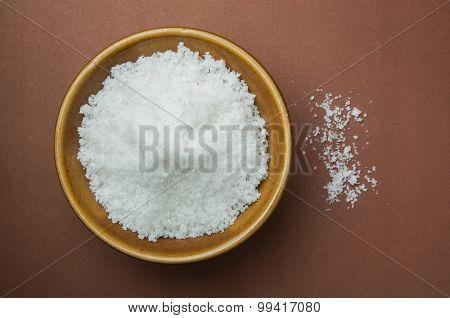salt in brown bowl on brown background .