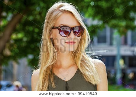 Young beautiful blonde woman in sunglasses, outdoors