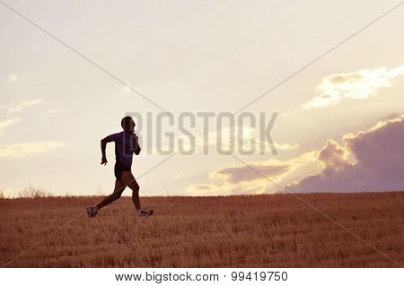 Profile Silhouette Of Young Man Running In Countryside Training In Summer Sunset