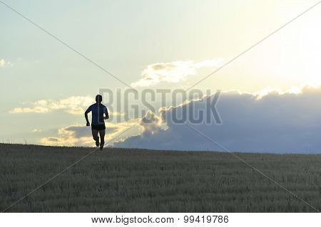 Frontal Silhouette Of Young Man Running In Countryside Training In Summer Sunset