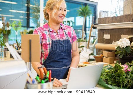 Smiling mature female florist using laptop at counter in flower shop