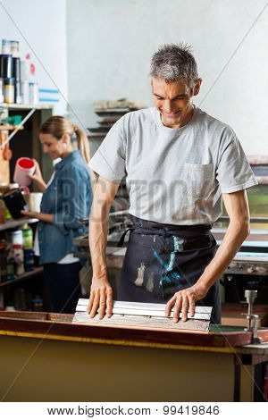 Smiling mature man using squeegee while female colleague working in background at factory