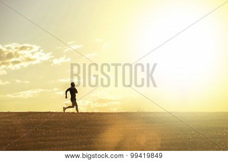 profile silhouette of young man running in countryside training cross country on sunset