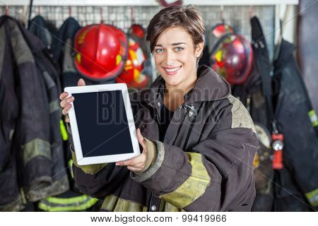 Portrait of beautiful firewoman showing digital tablet with blank screen at fire station