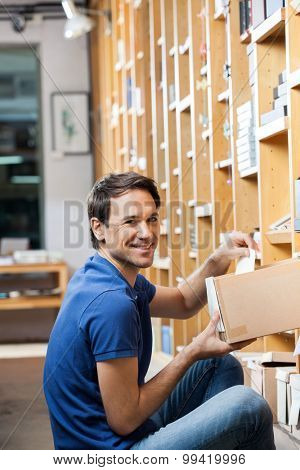 Portrait of happy mid adult customer removing paper from cardboard box in shop