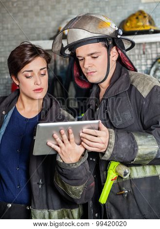 Young fireman and firewoman using tablet computer at fire station