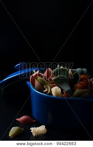 Colored spelt pasta in blue ceramic pot