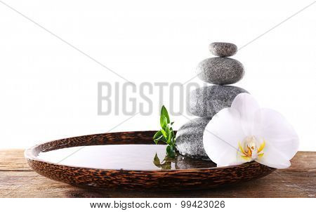 Spa stones with orchid and bamboo in wooden tray with water isolated on white
