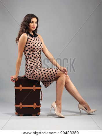 Retro style photo of young woman with suitcase on grey background