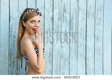 Beautiful girl with pretty smile on color wooden background