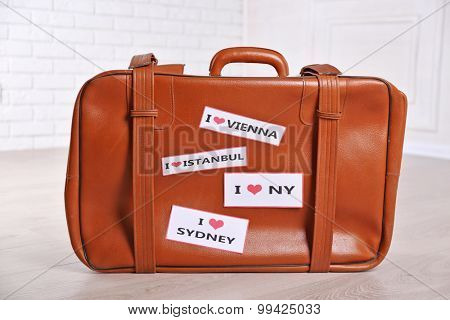 Suitcase with stickers on floor in room