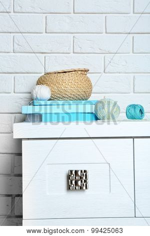 Books with decorative basket on brick wall background