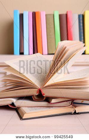 Opened books lying on bookshelf close-up