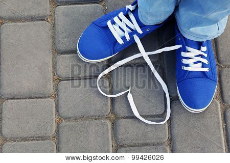 Female feet in gum shoes on asphalt background