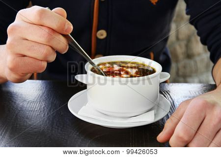 White bowl with borsch and male hands with spoon on wooden table, closeup