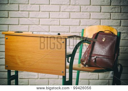 School desk and chair with bag on white brick wall background