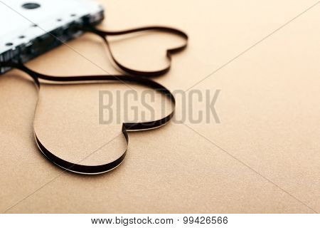 Audio cassette with magnetic tape in shape of hearts on brown background