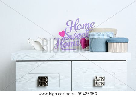 Textile boxes with decorative birds on wall background